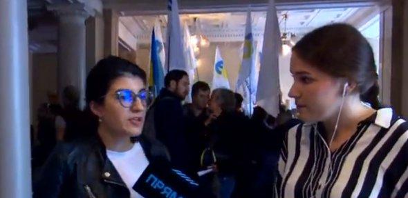 У приміщенні ДБР люди стоять з партійними і синьо-жовтими прапорами.