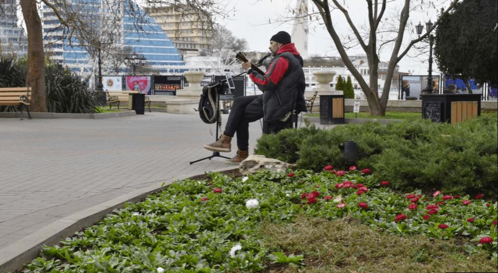 Вуличний музикант у компанії квітів на Приморському бульварі
